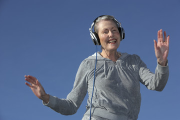 senior woman danving and listening through headphones