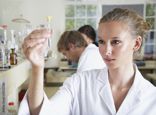 Woman in a busy laboratory holding up a small beaker