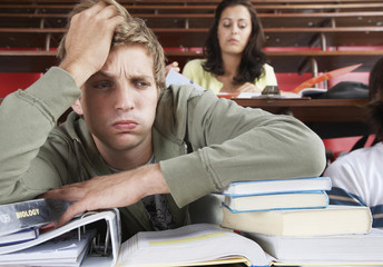 A frustrated male in a classroom with two students in background