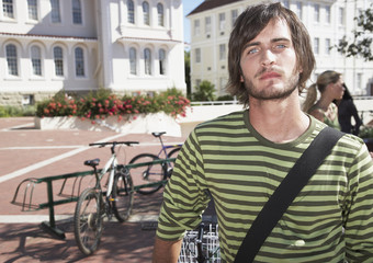 A young man standing by a bike rack