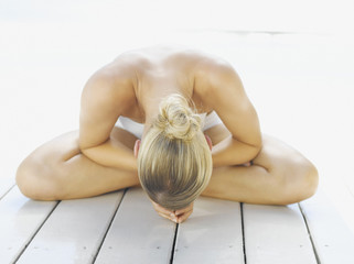 Woman sitting cross-legged with her head down