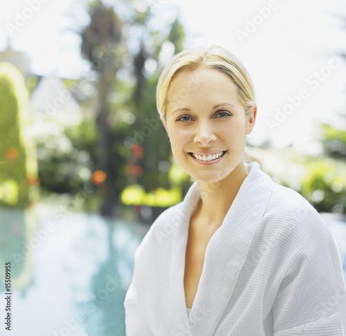 Woman relaxing in a bathrobe by a pool