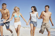 Four people running on the beach holding hands