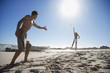 A young couple playing Frisbee at the beach
