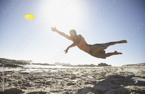 A man leaping through the air at the beach