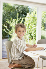 A young boy writing at a table smiling