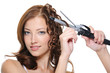 Curling female brunette hair with roller