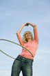 Young Woman With Hula Hoop Around Waist Smiling