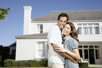 A couple embracing in front of a large home
