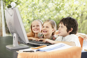 Three young kids using a computer together