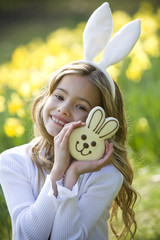 Young Girl Holding Chocolate Bunny Wearing Bunny Ears