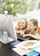 Two young girls using a computer together