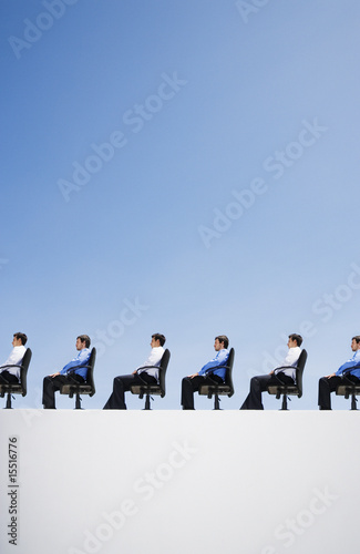 Line-up of businessmen in their office chairs