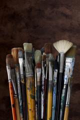 Artist paint brushes shot with dark textured background