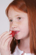Redhead girl eating strawberry