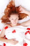 Beautiful girl in bed with red plumage poster