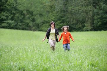 Jeunes enfants  souriants courant dans l'herbe