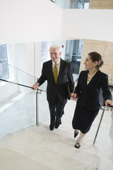 Businesswoman and senior executive walking up modern lobby stair