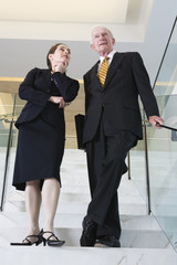 Businesswoman and senior executive standing on modern lobby stai