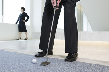 Businessman putting golf ball with woman executive in background