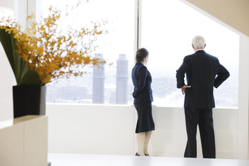 Executives looking out of office window at city view.