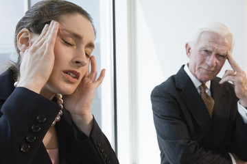 Businesswoman suffering from stress headache in an office.