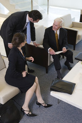 Team in lobby meeting to review paperwork with senior manager.