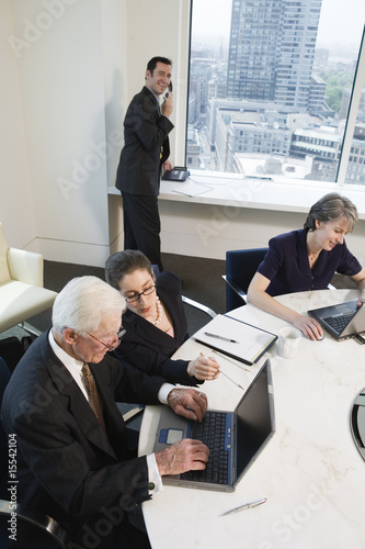 Four executives meeting with laptops in a conference room with a