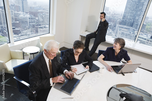 Four executives meeting in a conference room with a city view.