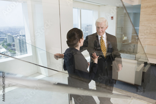 Senior executive in discussion with businesswoman on escalator.