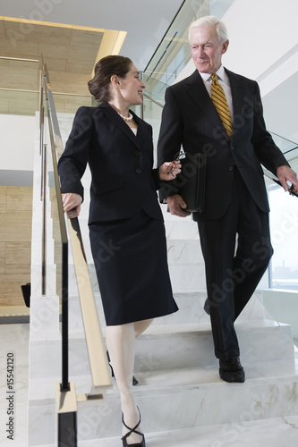 Senior executive with businesswoman walking down stairway.