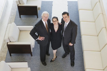 Trio of successful executives posing in lobby.