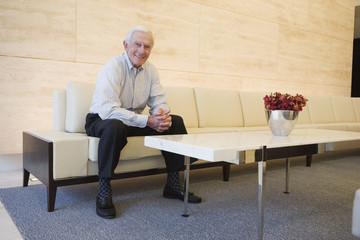 Smiling senior man seated in modern lobby.