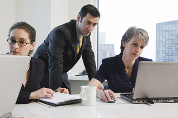 View of businesspeople in a meeting with laptops.