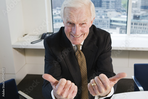 Senior businessman gesturing success in office.
