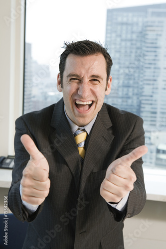 Portrait of happy executive giving thumbs up.