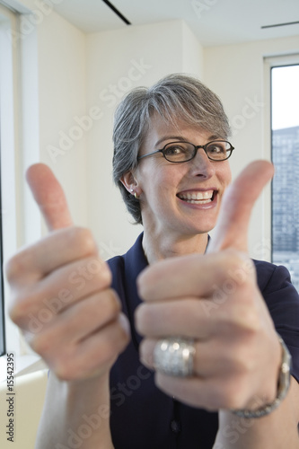 Portrait of happy businesswoman giving thumbs up.