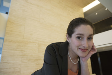 Smiling businesswoman sitting in lobby.