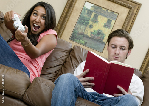 A man reading a book while his girlfriend plays video games