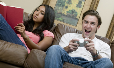 A woman reading a book while her boyfriend plays video games