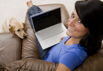 A woman and her dog relaxing on the couch