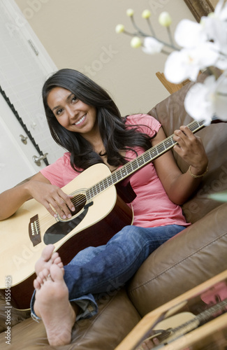 A beautiful woman playing acoustic guitar