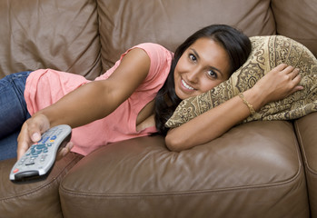 A beautiful woman watching television on the couch
