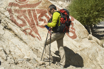 Hiker resting with a buddhist wallpaint