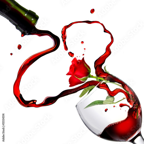 Heart from pouring red wine in goblet with red rose