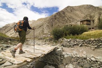 Woman hiker crossing a bridge in Markha valley trek