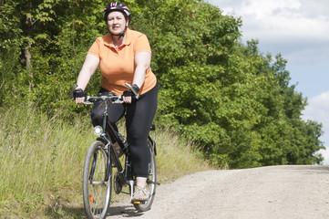 XXL-Model, übergewichtige Frau Rad fahren auf Waldweg