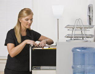Woman Looking Through Filing Cabinet