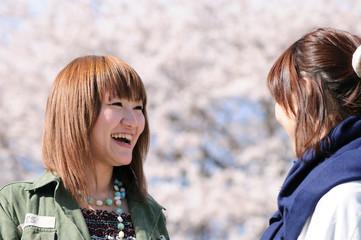 桜の前で話している女性