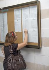 joven consultando notas en tablón